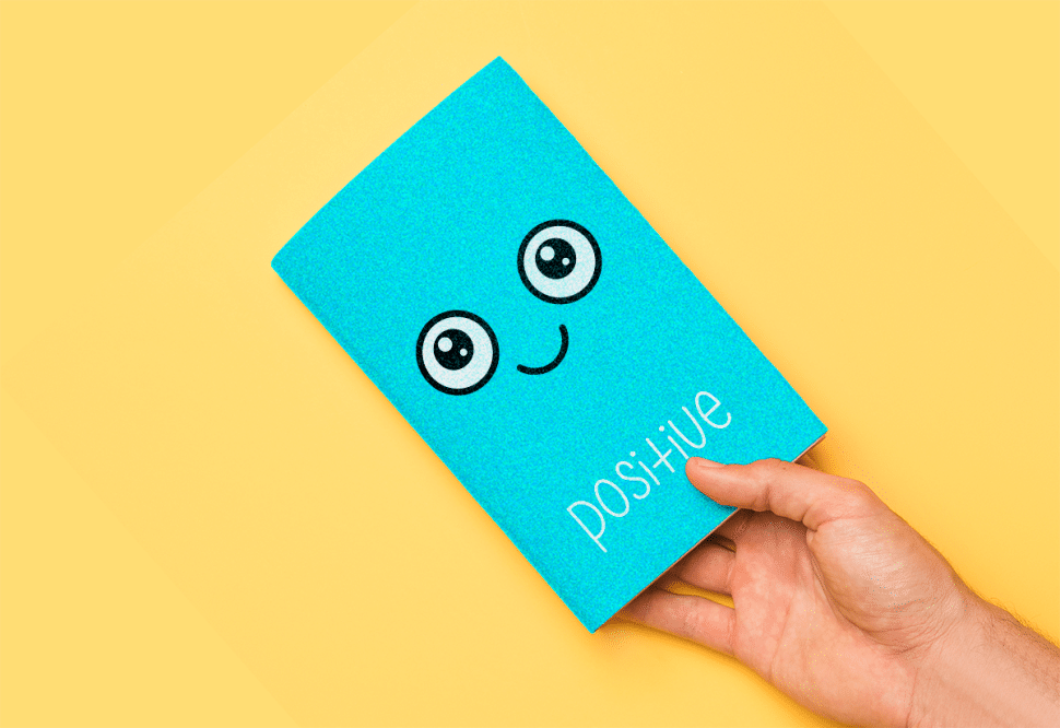 Small blue mindfulness journal for positive mood. Preview of a man holding free printable download.